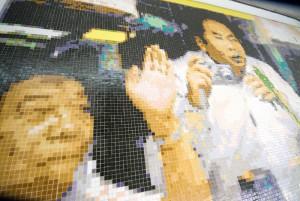 """Fliesenbild Barbara Krobath """"Drei Chinesen in der Qinghai-Tibet-Bahn"""" Mai bis September 2008 Eine Kooperation von KÖR Kunst im öffentlichen Raum Wien und den Wiener Linien U2 Station Schottentor, Liftgalerie über dem U2 Bahnsteig, 1010 Wien Das Fliesenbild von Barbara Krobath zeigt drei Touristen, die aus einem Zugfenster winken und fotografieren. Eine universale Wohlfühl-Chiffre, die auf den ersten Blick harmlos und heiter wirkt. Doch es handelt sich hier um einen besonderen Zug: Die Qinghai-Tibet-Bahn ist die höchstgelegene Eisenbahnstrecke der Erde (Scheitelpunkt: 5072 m). Das Prestigeprojekt der chinesischen Regierung, von dem schon Mao Tse Tung träumte, wurde am 1. Juli 2006 eröffnet und verbindet die Provinz Qinghai mit der Hauptstadt Lhasa des Autonomen Gebietes Tibet. Ist die Bahn ein Mittel, um immer mehr Chinesen auf dem Dach der Welt anzusiedeln und damit die Tibeter und ihre Kultur weiter an den Rand zu drängen? Wird sie im Notfall schnell Truppen nach Lhasa transportieren? Oder sollen wir das Bild als Vision einer Zukunft lesen, in der chinesische Touristen in ein freies Tibet kommen und einem stolzen Volk zuwinken? Das 19m2 große Bild der Drei Chinesen in der Qinghai-Tibet-Bahn ist aus ca. 40 000 Bisazza-Glasmosaikfliesen zusammengesetzt. www.koer.or.at"""